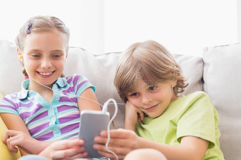 Música de escuta dos irmãos através do telefone celular em casa imagens de stock
