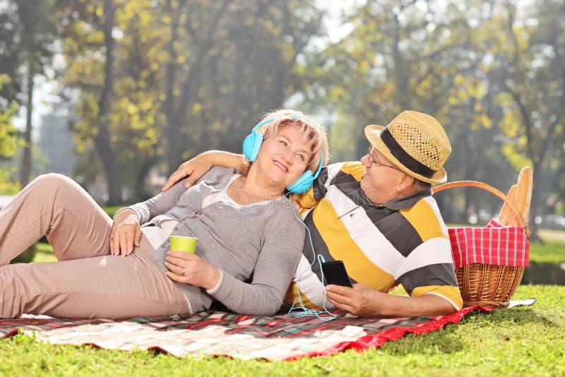 Música de escuta dos pares maduros em um piquenique no parque fotos de stock royalty free