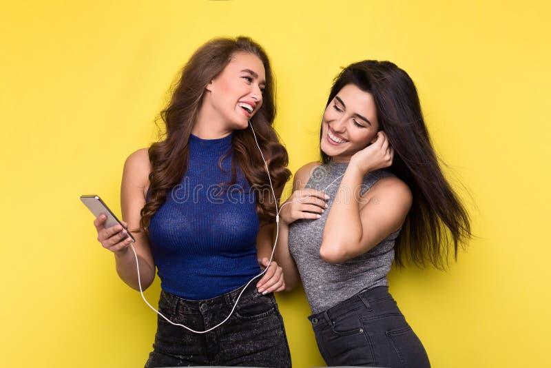 Música de escuta de duas mulheres em linha no smartphone imagens de stock royalty free