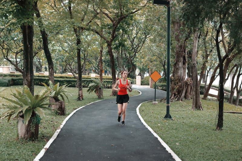 A música de escuta e o corredor da mulher asiática relaxado do corredor da aptidão malham no parque natural imagens de stock