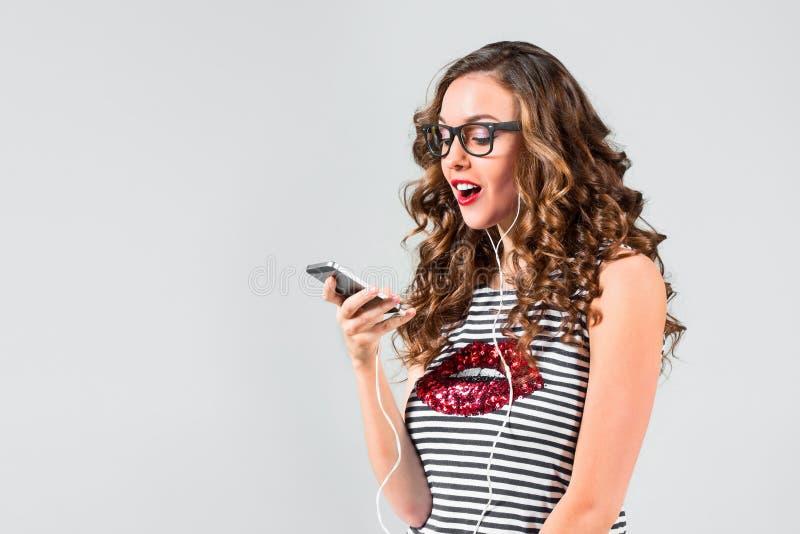 Música de escuta feliz da mulher nova com auscultadores fotos de stock