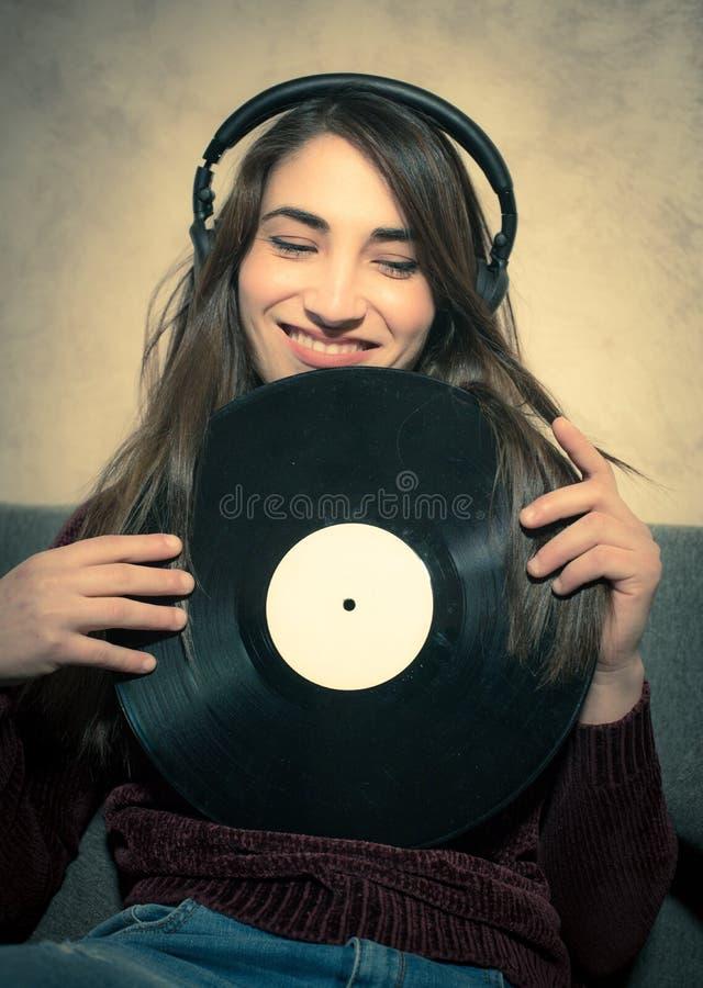 Música de escuta de sorriso nova da mulher com registros de vinil fotografia de stock royalty free
