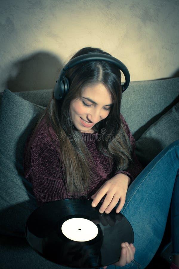 Música de escuta de sorriso nova da mulher com registros de vinil fotos de stock