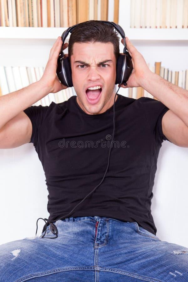 Música de escuta surpreendida e chocada do homem ocasional em fones de ouvido foto de stock
