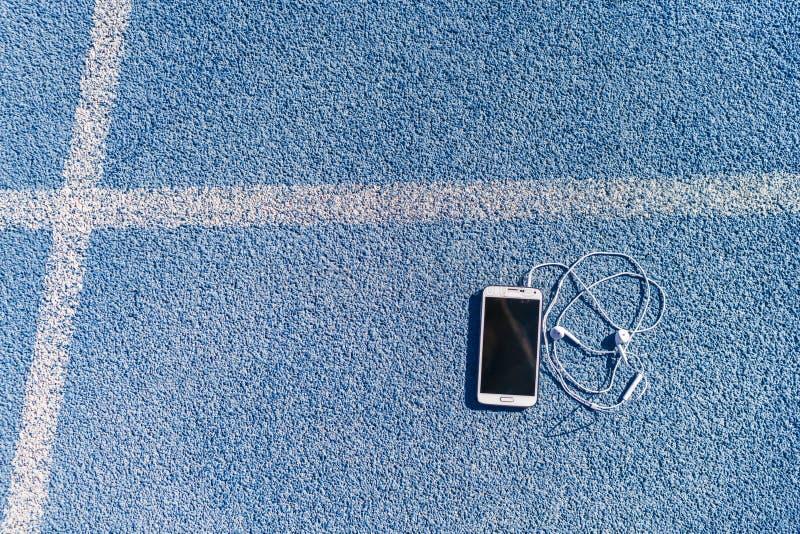 Música de funcionamiento del teléfono móvil del carril del atletismo fotos de archivo libres de regalías
