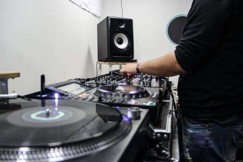 Música de jogo e de mistura do indivíduo novo em um controlador do DJ foto de stock
