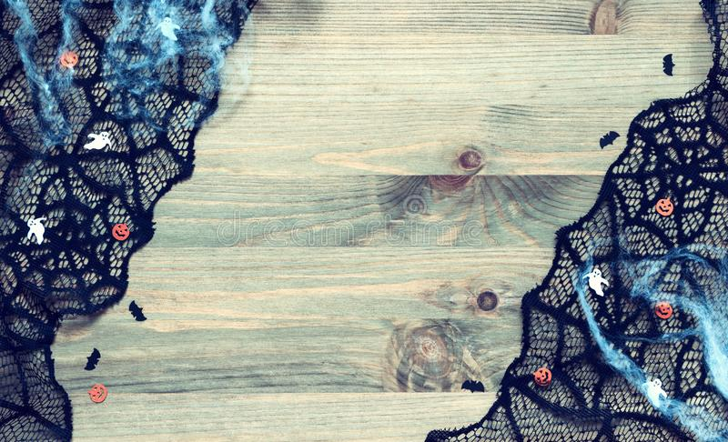 Música de la noche Web de araña, cordón negro de la telaraña y decoraciones los símbolos de Halloween en el fondo de madera fotos de archivo