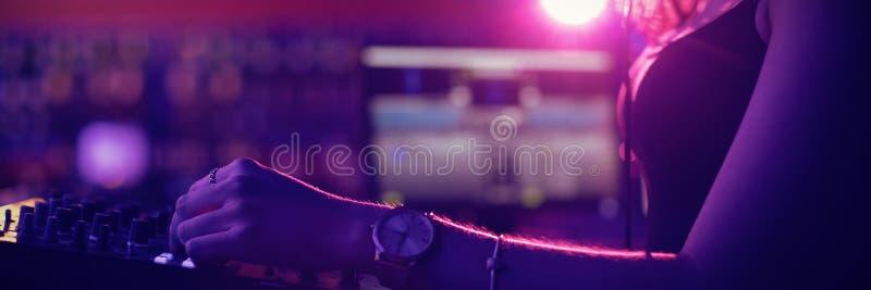Música de mistura fêmea do DJ na barra foto de stock royalty free