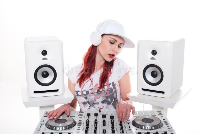 Música de mistura fêmea nova usando o misturador do DJ foto de stock