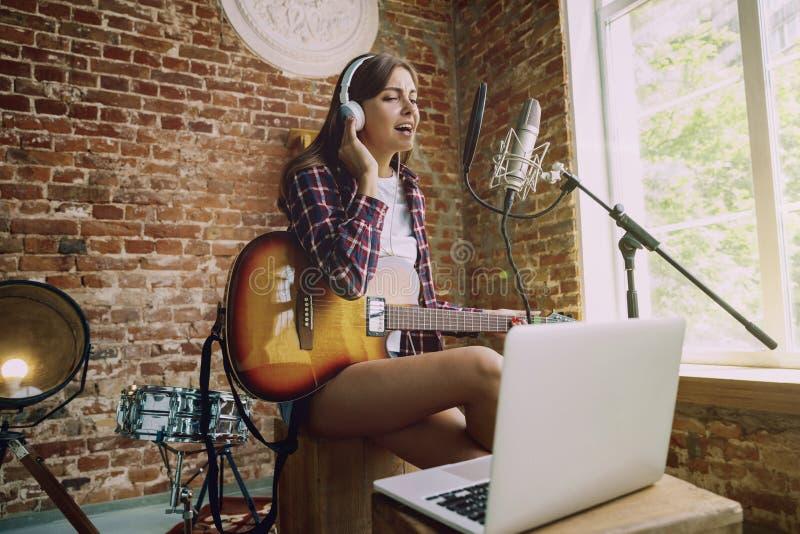 Música de registración de la mujer, tocando la guitarra y cantando en casa fotografía de archivo libre de regalías