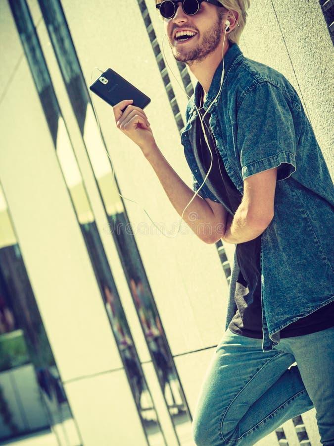 Música de risa y que escucha del hombre del inconformista a través de los auriculares imagenes de archivo
