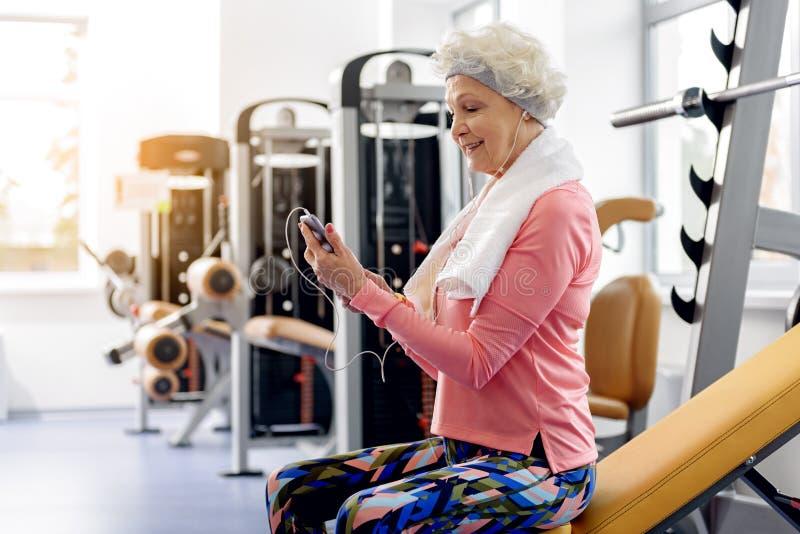 Música de sorriso da audição da avó no fitness center imagens de stock royalty free
