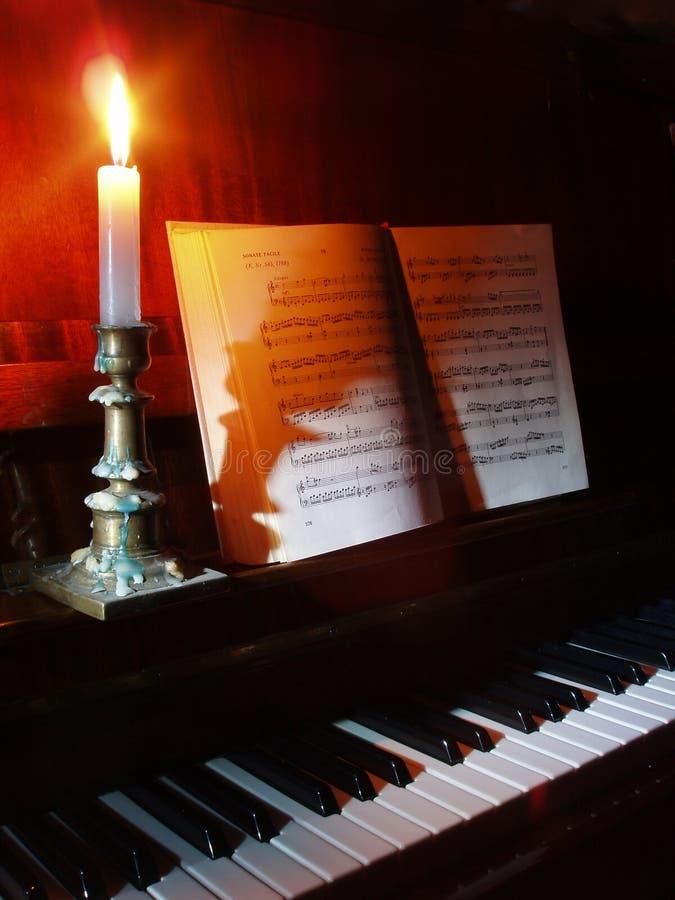 Música del piano y de hoja en la iluminación de la vela fotografía de archivo libre de regalías