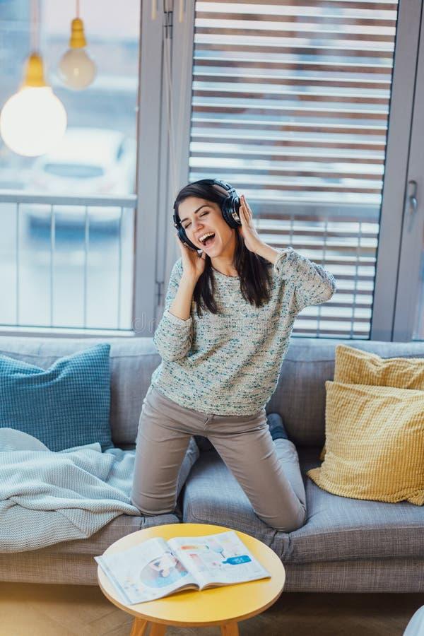 Música do canto com emoção Capacidades vocais praticando Melhorando a escala Mulher alegre que escuta a música com grandes fones  imagem de stock