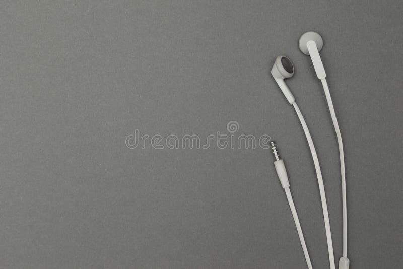 Música dos fones de ouvido em um fundo cinzento imagens de stock royalty free
