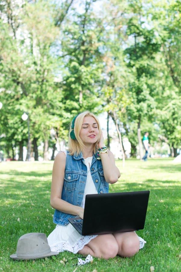 Música feliz de la transferencia de la mujer al aire libre con el ordenador portátil fotografía de archivo