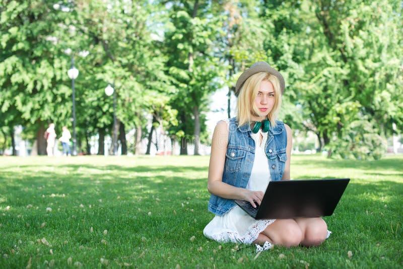 Música feliz de la transferencia de la mujer al aire libre con el ordenador portátil foto de archivo libre de regalías