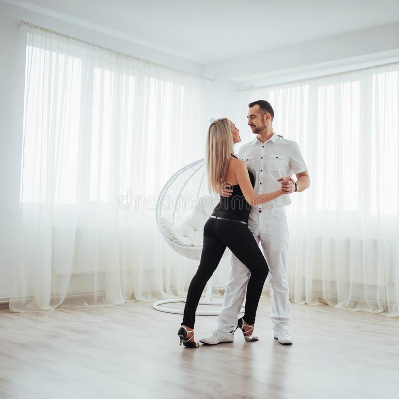 Música latin de dança dos pares novos: Bachata, merengue, salsa Pose da elegância dois na sala branca fotografia de stock