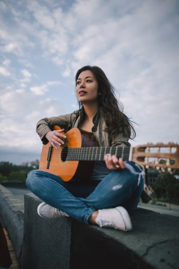 Música livre Jogos fêmeas do guitarrista na rua foto de stock