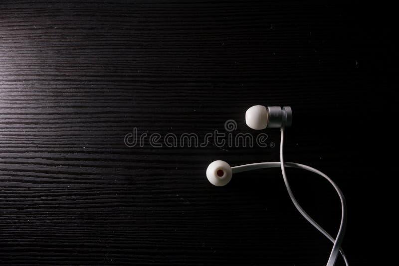 A música moderna mínima pura branca dos fones de ouvido prende a mesa preta imagem de stock royalty free