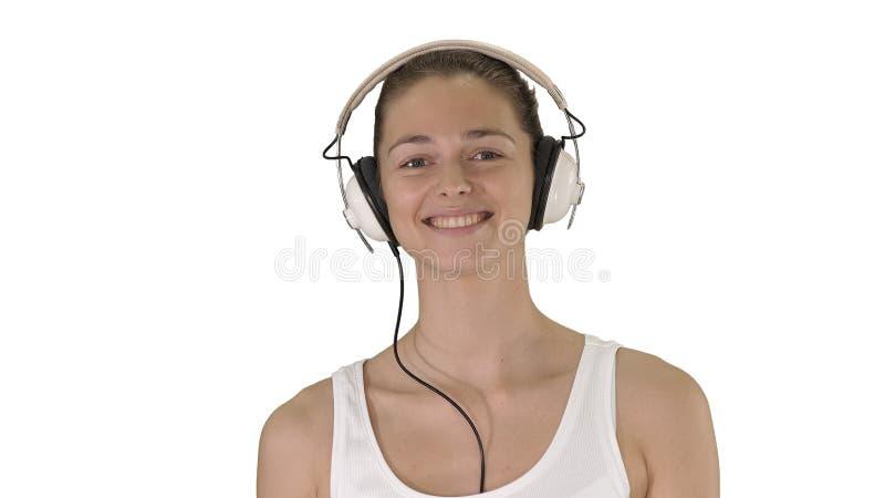 Música, povos e conceito da tecnologia - mulher de sorriso feliz com fones de ouvido que anda no fundo branco foto de stock