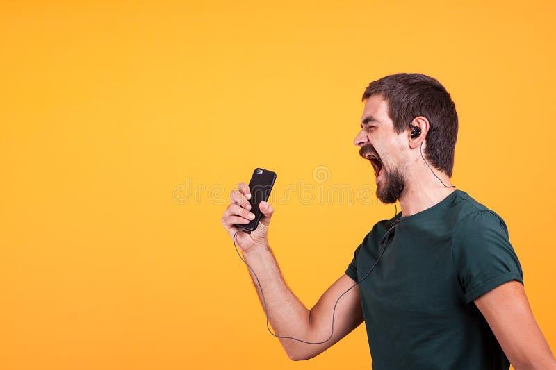 Música que escucha alegre fresca del hombre joven en sus auriculares imagen de archivo libre de regalías