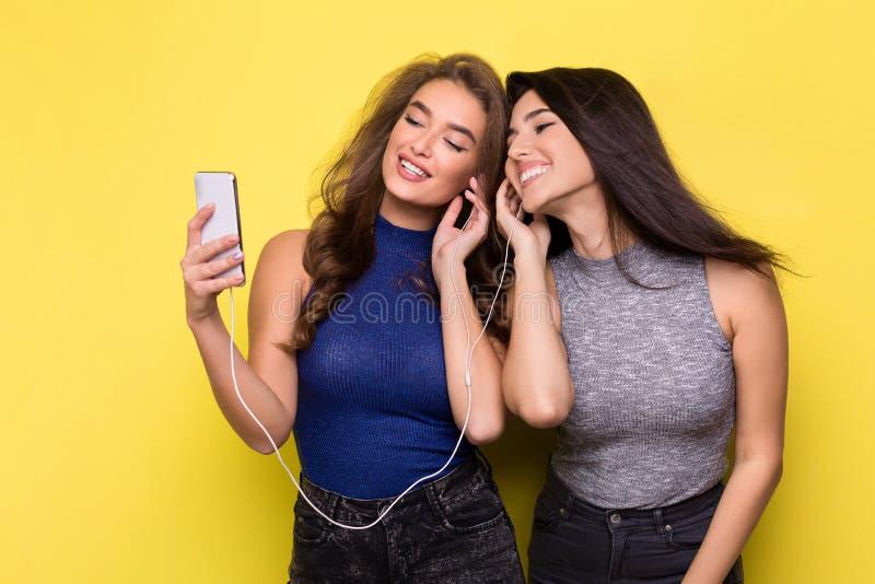 Música que escucha de dos mujeres en línea en smartphone imagenes de archivo