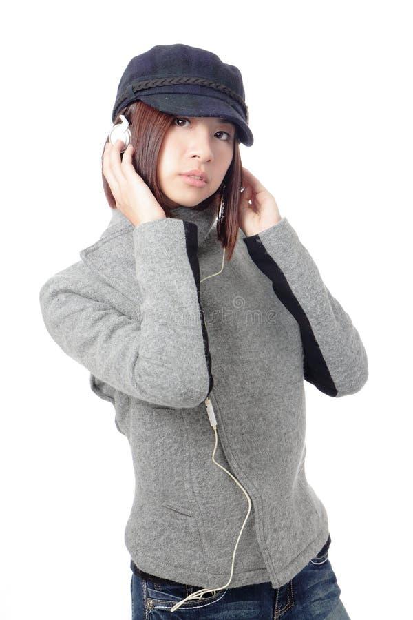 Música que escucha de la chica joven en auriculares foto de archivo libre de regalías