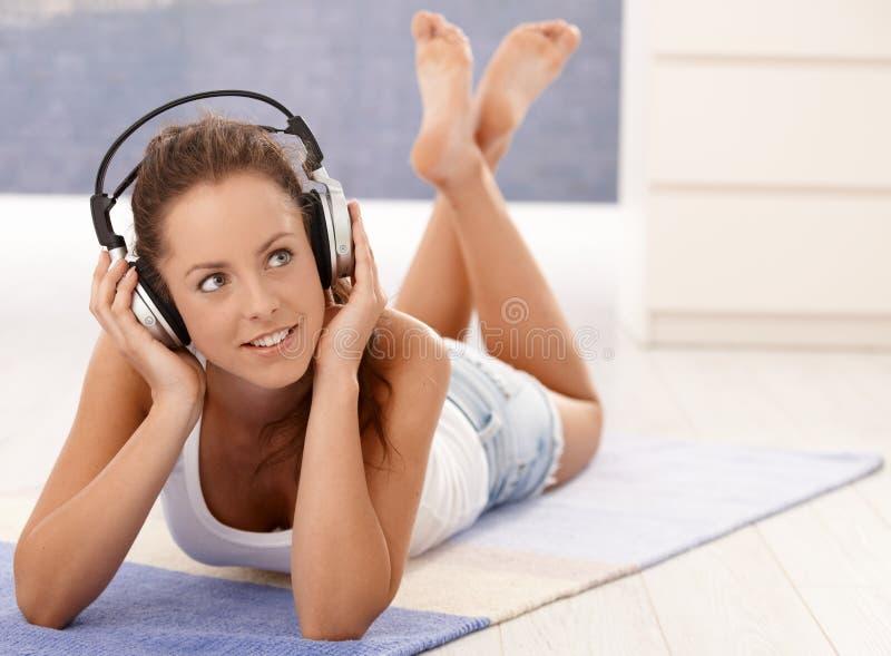 Música que escucha de la muchacha atractiva que pone en suelo foto de archivo libre de regalías