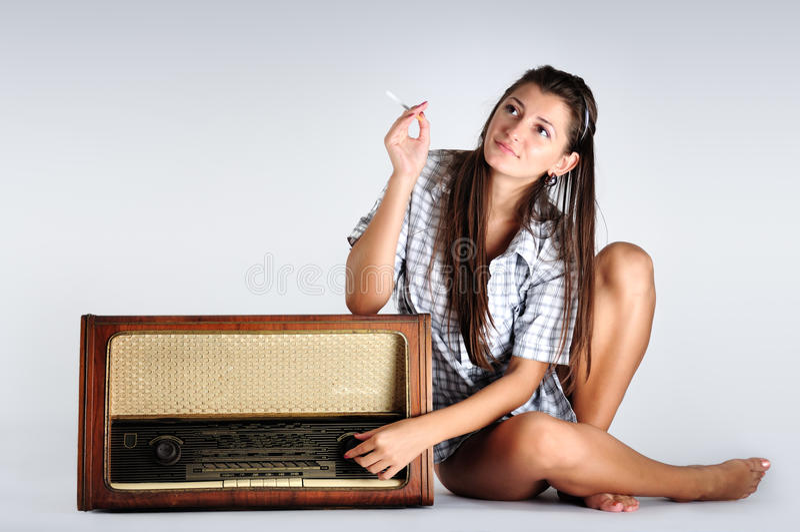 Música que escucha de la muchacha bonita en radio y el pensamiento fotografía de archivo libre de regalías
