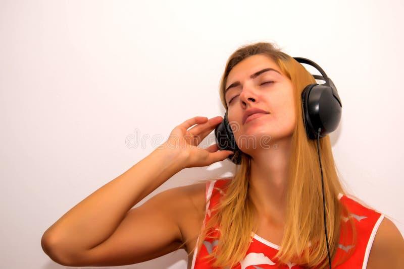 Música que escucha de la muchacha en los auriculares imagen de archivo libre de regalías