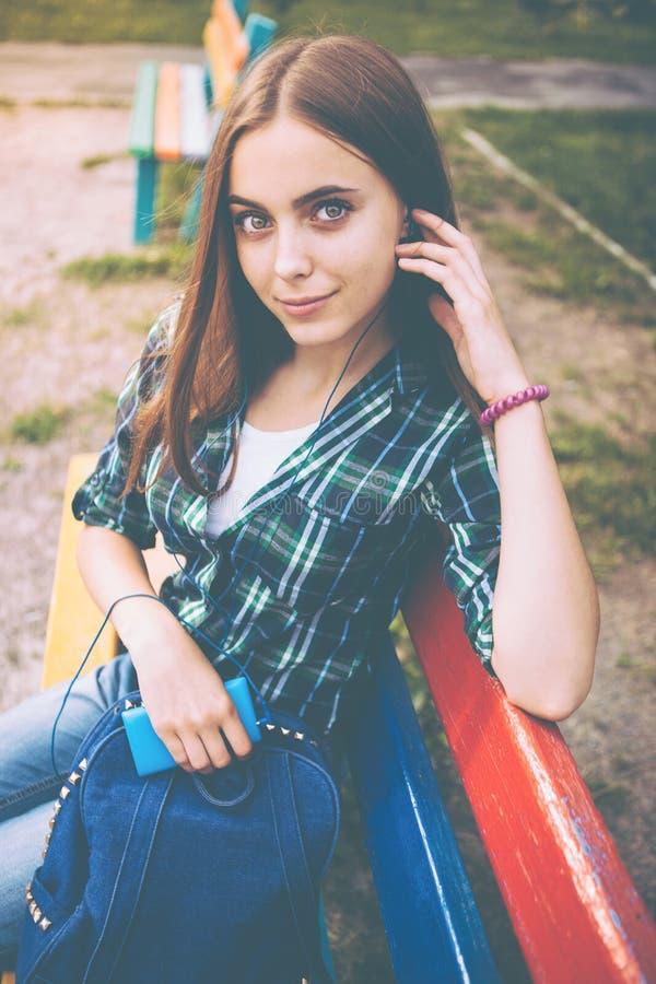 Música que escucha de la muchacha hermosa con los auriculares al aire libre imagen de archivo