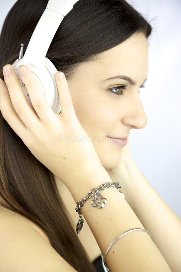 Música que escucha de la muchacha linda con los auriculares blancos imagen de archivo