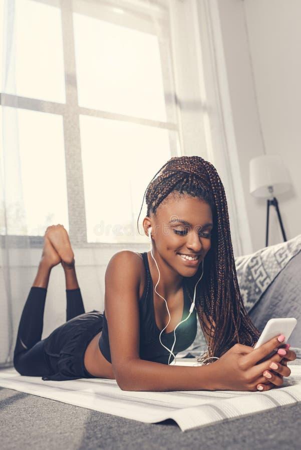 música que escucha de la mujer afroamericana juguetona con smartphone y los auriculares fotos de archivo libres de regalías