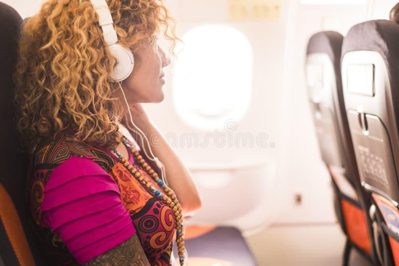 Música que escucha de la mujer atractiva alternativa caucásica del inconformista por los auriculares fliying en el aeroplano a vi fotografía de archivo libre de regalías