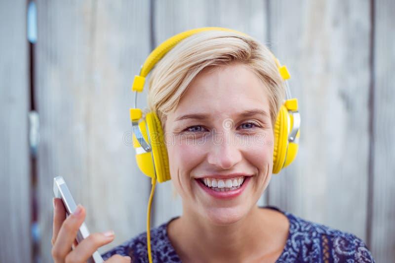 Música que escucha de la mujer bastante rubia con su teléfono móvil fotos de archivo libres de regalías