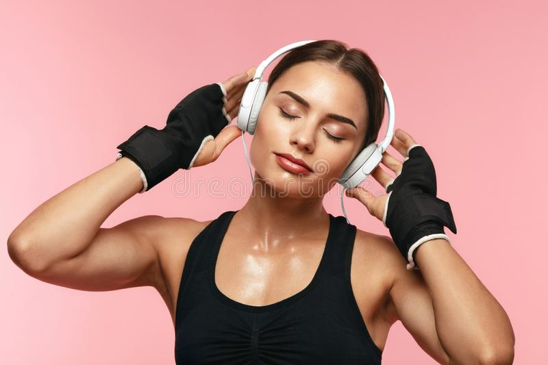 Música que escucha de la mujer del deporte en auriculares en el entrenamiento imagenes de archivo