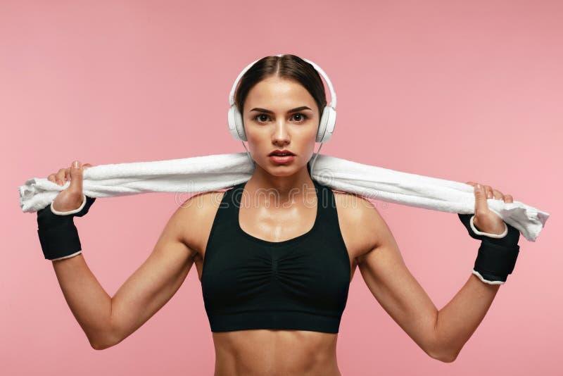 Música que escucha de la mujer del deporte en auriculares en el entrenamiento foto de archivo libre de regalías