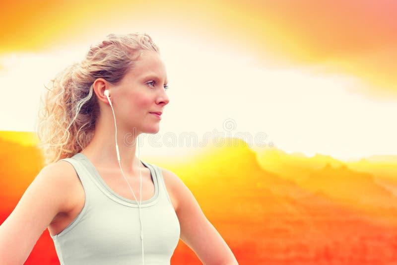 Música que escucha de la mujer deportiva confiada en la puesta del sol imagenes de archivo
