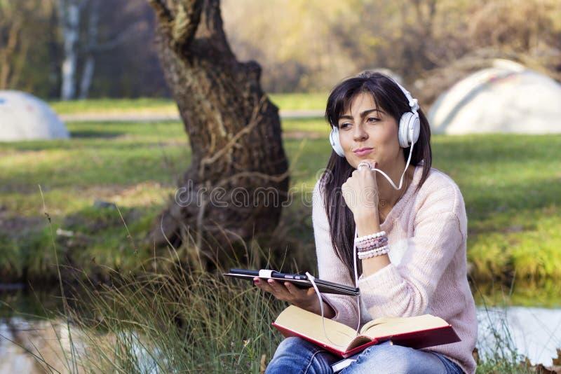 Música que escucha de la mujer joven con su tableta en un parque del otoño fotos de archivo