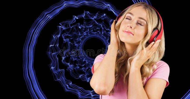 Música que escucha de la mujer joven a través de los auriculares contra fondo abstracto foto de archivo