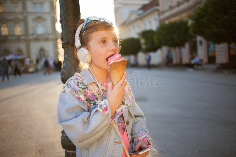 Música que escucha de la niña en la calle y la consumición del helado imágenes de archivo libres de regalías