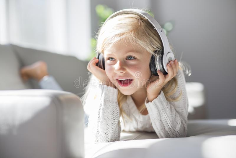Música que escucha de la niña feliz que miente en la sala de estar del sofá foto de archivo libre de regalías