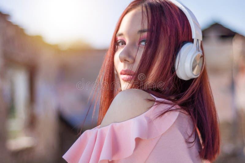 Música que escucha de la señora linda de los pelirrojos con los auriculares en fondo al aire libre borroso en puesta del sol imagenes de archivo