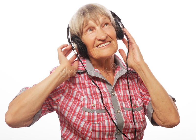 Música que escucha de la señora mayor divertida imagen de archivo libre de regalías