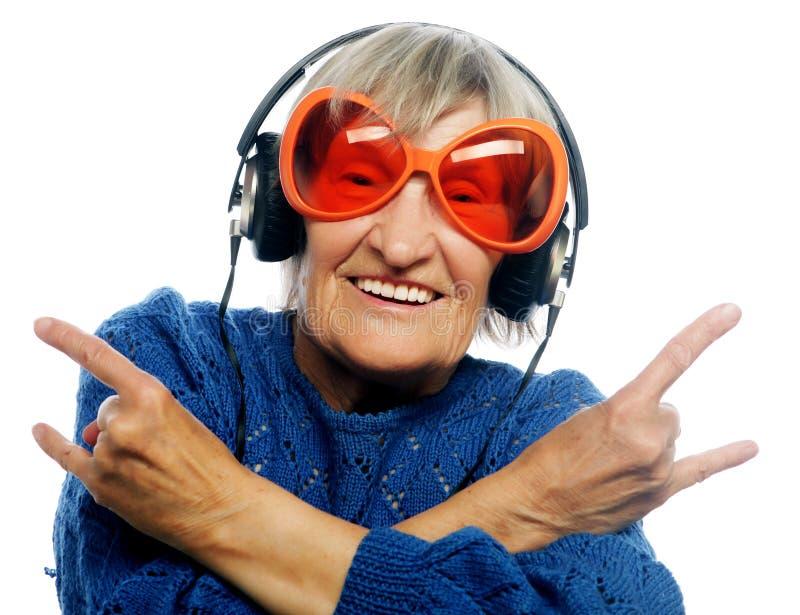 Música que escucha de la señora mayor divertida y el mostrar pulgares para arriba imágenes de archivo libres de regalías