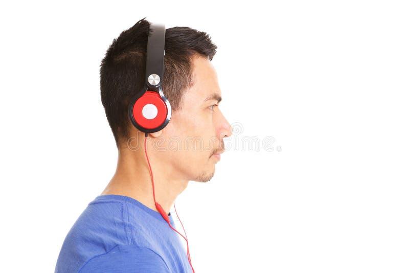Música que escucha de un más viejo hombre asiático en los auriculares fotos de archivo libres de regalías