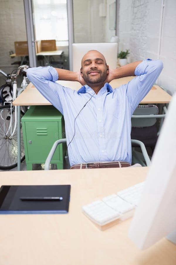 Música que escucha del hombre de negocios relajado en el escritorio fotos de archivo libres de regalías