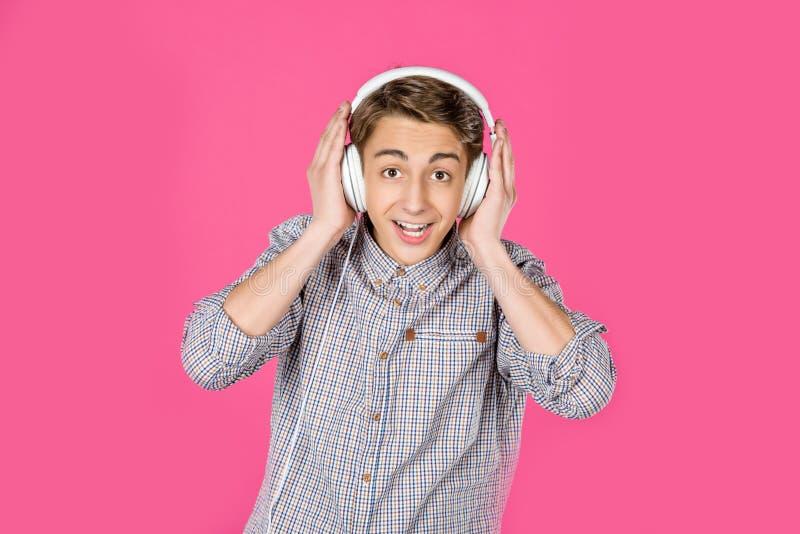 música que escucha del muchacho adolescente emocionado con los auriculares imagenes de archivo