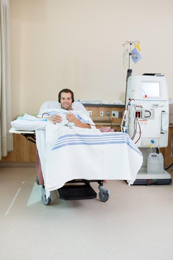 Música que escucha del paciente mientras que recibe renal foto de archivo